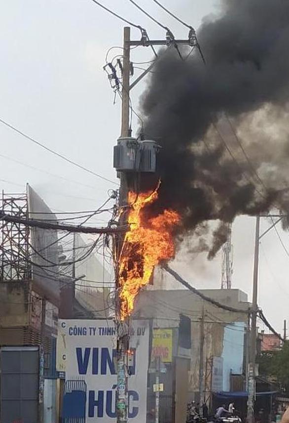 Cột điện ven quốc lộ ở TP.HCM bốc cháy ngùn ngụt kèm theo nhiều tiếng nổ - Ảnh 2.