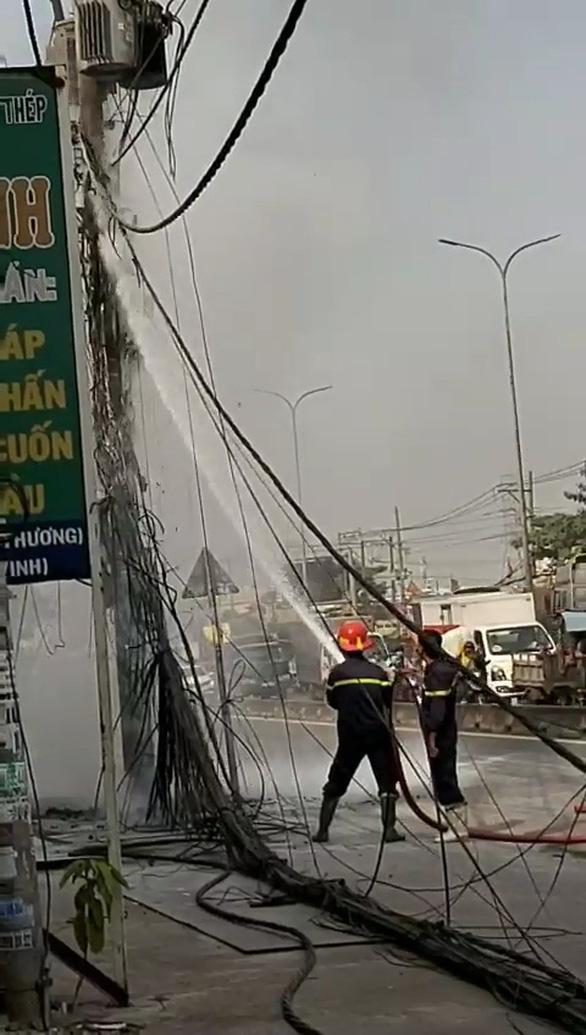 Cột điện ven quốc lộ ở TP.HCM bốc cháy ngùn ngụt kèm theo nhiều tiếng nổ - Ảnh 3.