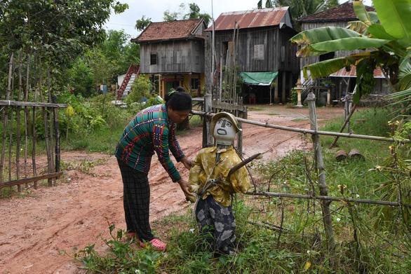 Dân Campuchia đuổi corona bằng bù nhìn cầm súng trước cửa nhà - Ảnh 1.