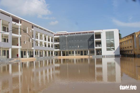 Trường mới xây, chưa bàn giao nhưng cứ mưa lại ngập lút sân - Ảnh 1.