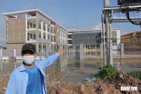 Trường mới xây, chưa bàn giao nhưng cứ mưa lại ngập lút sân - Ảnh 2.
