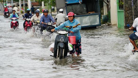 Triều cường đỉnh gặp mưa lớn, người dân TP.HCM đề phòng ngập nước, vỡ bờ bao - Ảnh 1.