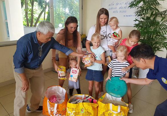 Hai nữ du khách Nga mắc kẹt tại Việt Nam bế con đi mua đồ cứu trợ dân vùng lũ - Ảnh 1.