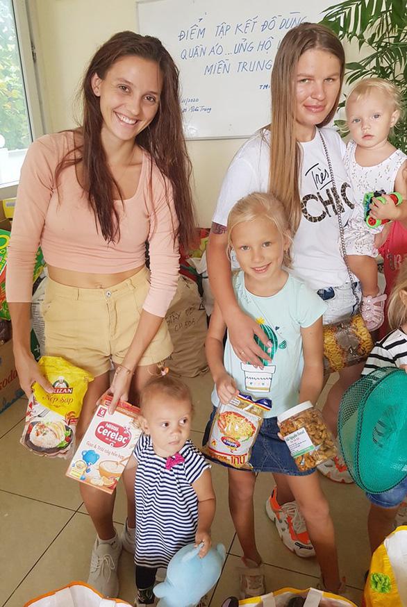 Hai nữ du khách Nga mắc kẹt tại Việt Nam bế con đi mua đồ cứu trợ dân vùng lũ - Ảnh 2.