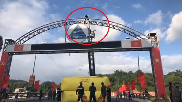 Cảnh sát bơm phao hơi, điều xe thang để giải cứu thanh niên leo cổng chào - Ảnh 2.