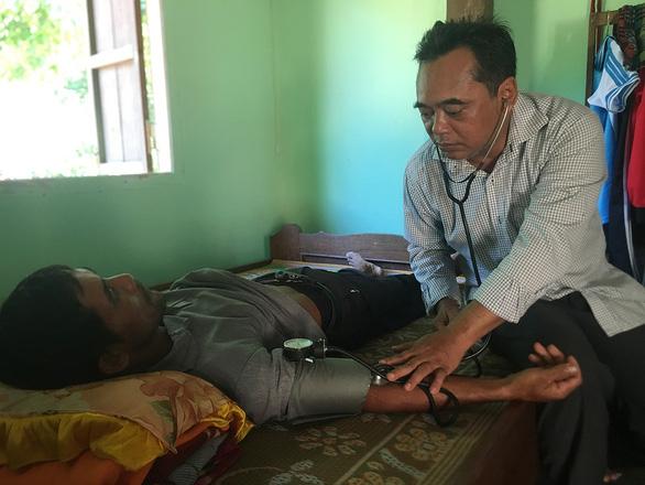 Ông bí thư huyện Mấu Văn Phi chạy xe máy cà tàng khám bệnh cho bà con - Ảnh 1.
