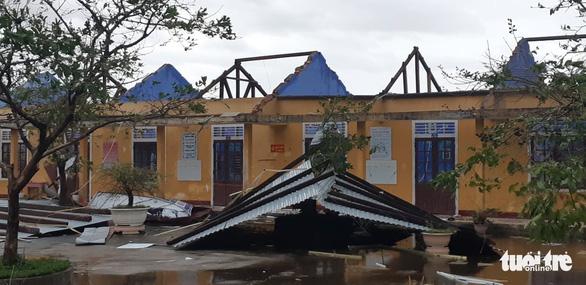 Bão vào miền Trung, mưa lớn, cây bật gốc, trường học tốc mái - Ảnh 1.