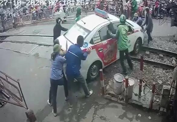 Cố tình vượt rào chắn đường sắt, tài xế taxi bị phạt nặng - Ảnh 2.