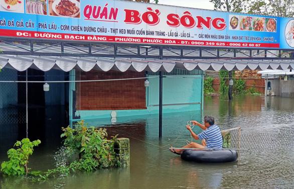 Mưa lớn, hồ xả lũ, một số khu vực tại Tam Kỳ ngập nặng, dân dùng thuyền đi lại - Ảnh 1.