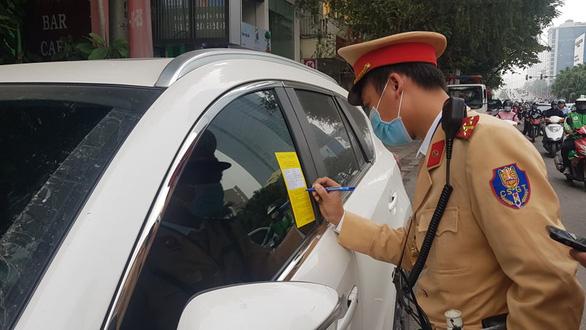 Cảnh sát giao thông Hà Nội dán thông báo phạt nguội trên kính ôtô - Ảnh 1.