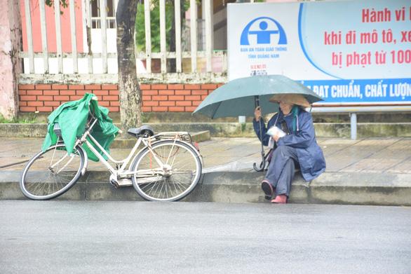 Những người già bán vé số đội mưa, co ro trong giá rét để mưu sinh - Ảnh 1.