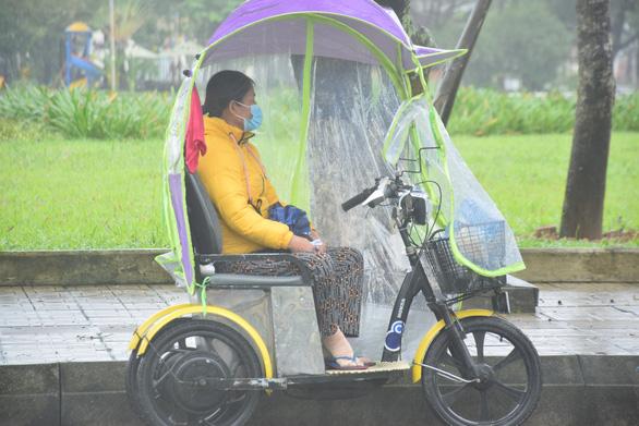 Những người già bán vé số đội mưa, co ro trong giá rét để mưu sinh - Ảnh 2.