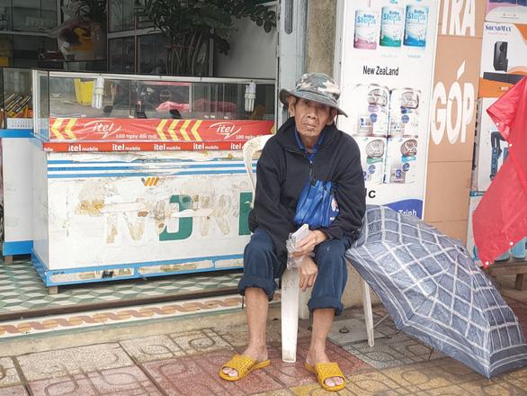Những người già bán vé số đội mưa, co ro trong giá rét để mưu sinh - Ảnh 5.