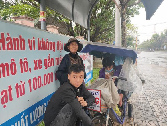Những người già bán vé số đội mưa, co ro trong giá rét để mưu sinh - Ảnh 4.