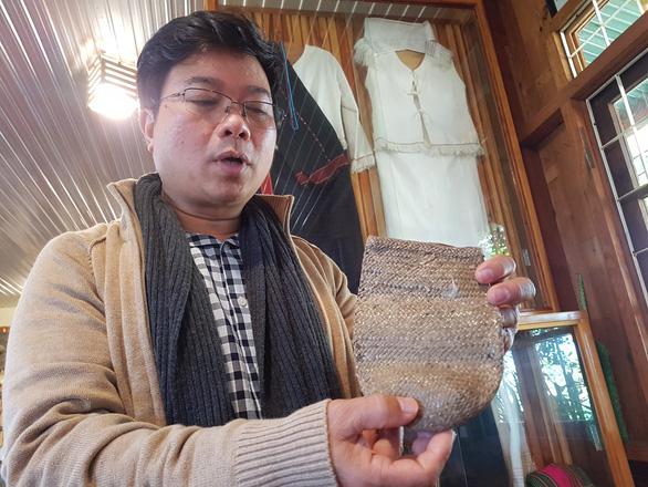 Cha Hung Long giới thiệu cái túi đựng cơm người Churu mang theo khi đi làm đồng - Ảnh: THÁI LỘC