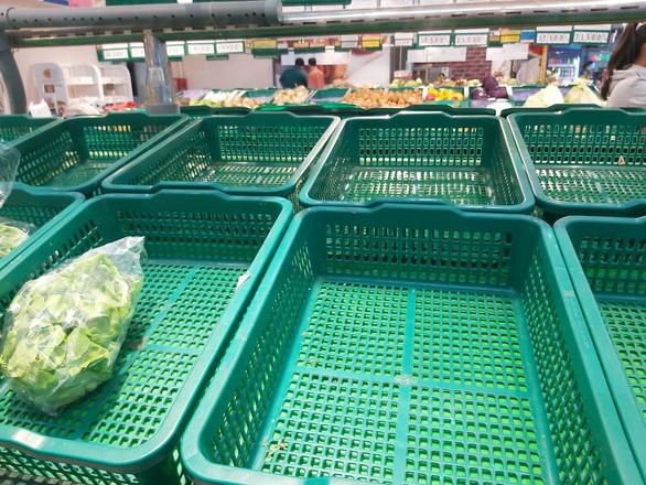Nhiều khay hàng thiết yếu tại các siêu thị ở TP.HCM bị vét sạch - Ảnh 1.