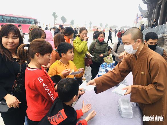 Dành sinh nhật đứng phát khẩu trang cho người dân tới chùa Tam Chúc - Ảnh 2.
