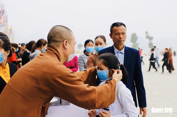 Dành sinh nhật đứng phát khẩu trang cho người dân tới chùa Tam Chúc - Ảnh 1.