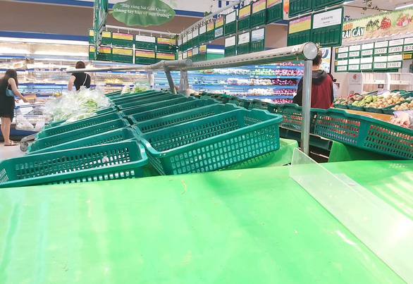 Nhiều khay hàng thiết yếu tại các siêu thị ở TP.HCM bị vét sạch - Ảnh 2.