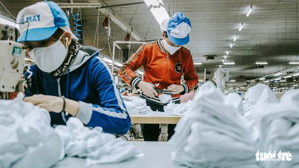 Vào nhà máy làm khẩu trang phòng virus corona, công nhân tăng ca gấp rưỡi - Ảnh 3.