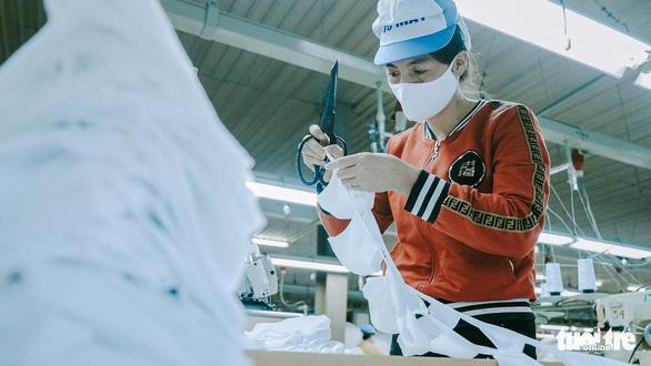 Vào nhà máy làm khẩu trang phòng virus corona, công nhân tăng ca gấp rưỡi - Ảnh 11.