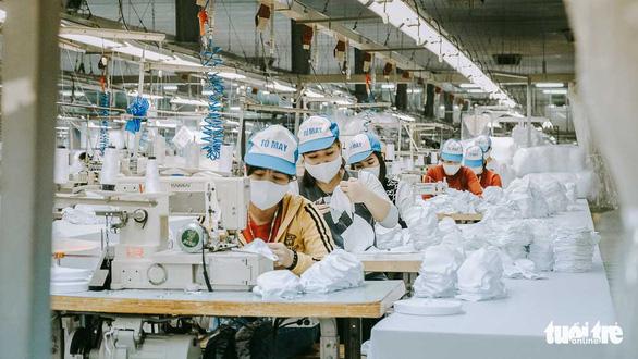 Vào nhà máy làm khẩu trang phòng virus corona, công nhân tăng ca gấp rưỡi - Ảnh 1.