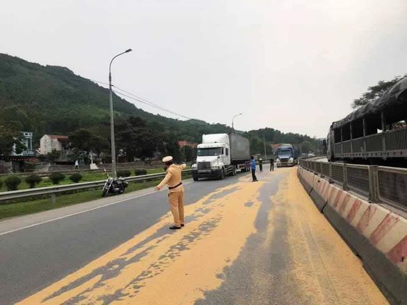 Cảnh sát giao thông và người dân giúp tài xế gom 4 tấn đỗ tương rớt xuống đường - Ảnh 1.
