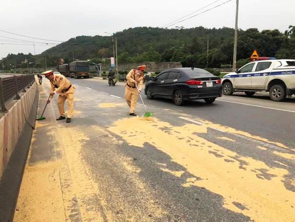 Cảnh sát giao thông và người dân giúp tài xế gom 4 tấn đỗ tương rớt xuống đường - Ảnh 4.