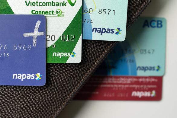 Các ngân hàng khẩn trương giảm tiếp phí chuyển tiền cho khách - Ảnh 1.