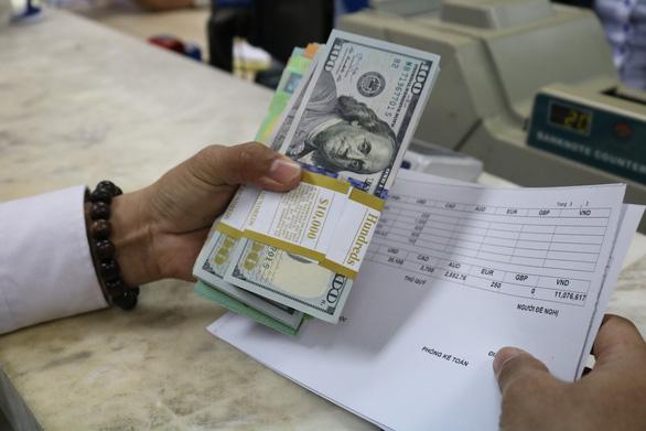 Giá USD tự do hạ nhiệt, USD ngân hàng lại nhích lên - Ảnh 1.