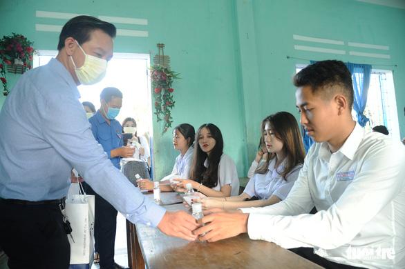 Sinh viên nhận khẩu trang, dung dịch sát khuẩn ngày đầu đi học lại - Ảnh 9.