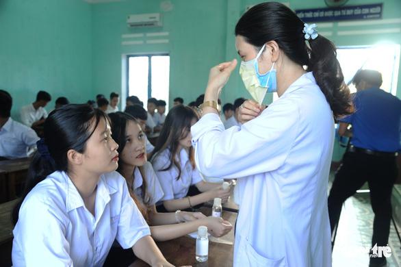 Sinh viên nhận khẩu trang, dung dịch sát khuẩn ngày đầu đi học lại - Ảnh 11.