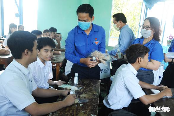 Sinh viên nhận khẩu trang, dung dịch sát khuẩn ngày đầu đi học lại - Ảnh 12.