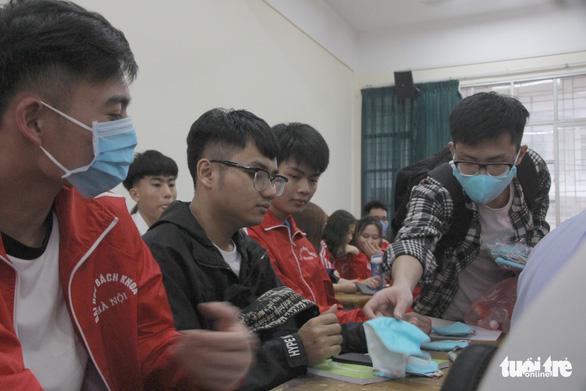 Sinh viên nhận khẩu trang, dung dịch sát khuẩn ngày đầu đi học lại - Ảnh 2.
