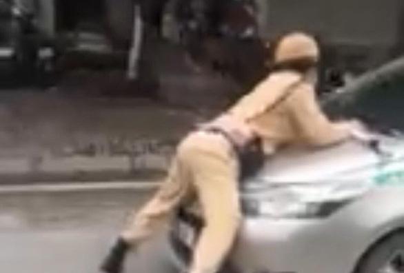 Tạm giữ hình sự tài xế taxi hất cảnh sát giao thông lên nắp capô - Ảnh 2.