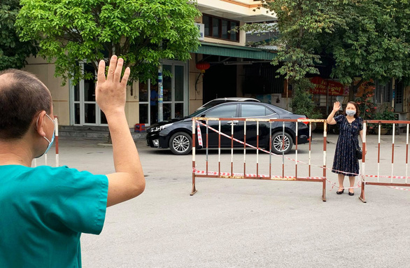 Vợ thăm chồng là giám đốc bệnh viện qua hàng rào cách ly - Ảnh 1.