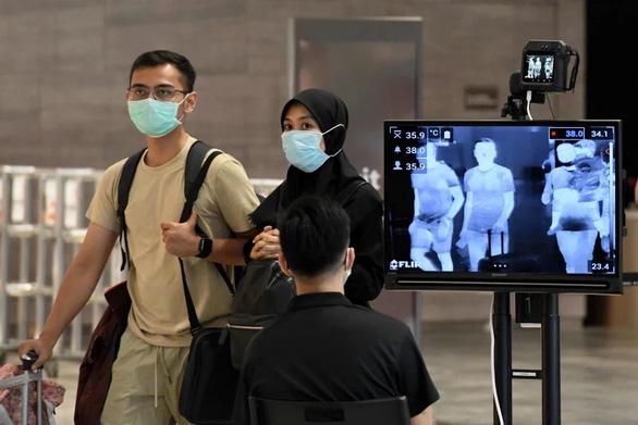 WHO khuyến cáo theo dõi khách ngồi gần người bệnh COVID-19 trên máy bay - Ảnh 1.