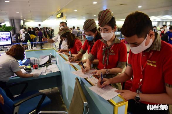 Xếp hàng chờ khai, nộp thông tin khai báo y tế ở sân bay Tân Sơn Nhất - Ảnh 1.