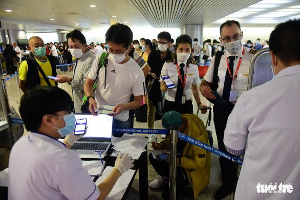 Xếp hàng chờ khai, nộp thông tin khai báo y tế ở sân bay Tân Sơn Nhất - Ảnh 4.
