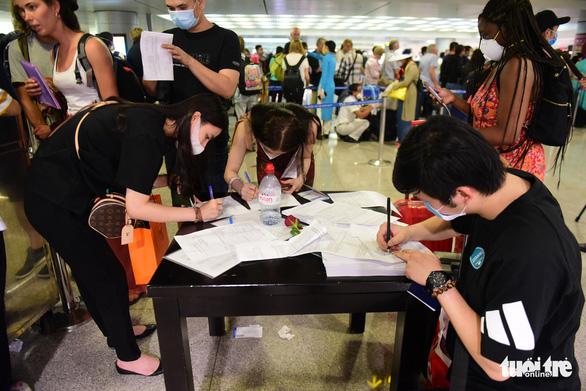 Xếp hàng chờ khai, nộp thông tin khai báo y tế ở sân bay Tân Sơn Nhất - Ảnh 5.