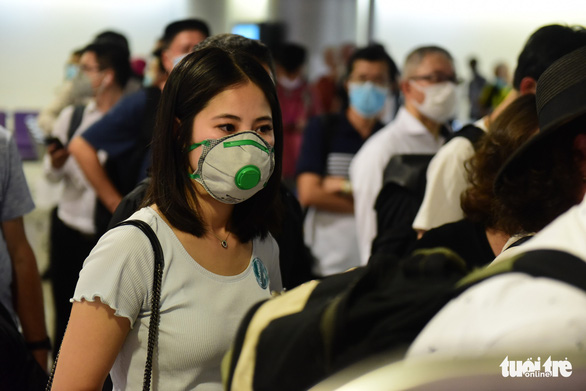 Xếp hàng chờ khai, nộp thông tin khai báo y tế ở sân bay Tân Sơn Nhất - Ảnh 7.