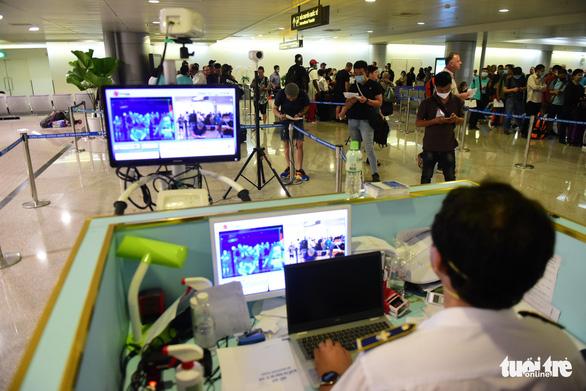Xếp hàng chờ khai, nộp thông tin khai báo y tế ở sân bay Tân Sơn Nhất - Ảnh 9.