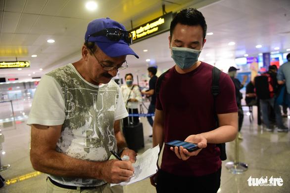 Xếp hàng chờ khai, nộp thông tin khai báo y tế ở sân bay Tân Sơn Nhất - Ảnh 3.