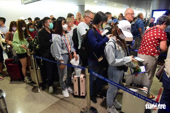 Xếp hàng chờ khai, nộp thông tin khai báo y tế ở sân bay Tân Sơn Nhất - Ảnh 10.
