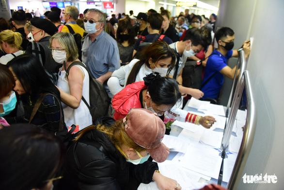 Xếp hàng chờ khai, nộp thông tin khai báo y tế ở sân bay Tân Sơn Nhất - Ảnh 11.