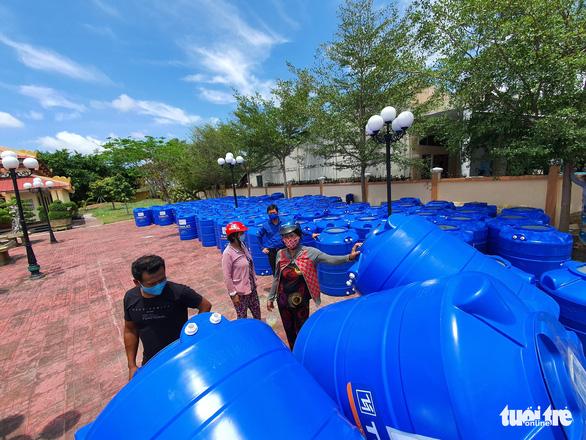 Người dân xã Long Điền nhận bồn chứa nước do bạn đọc báoTuổi Trẻđóng góp ngày 18-4 - Ảnh: CHÍ QUỐC