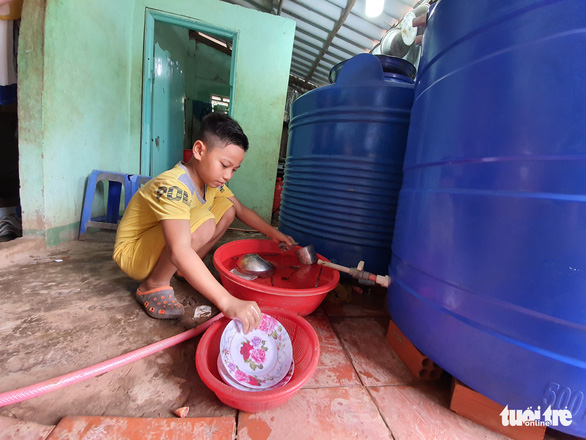Cháu Nguyễn Thái An (xã Long Điền) rửa chén phụ gia đình từ bồn chứa do bạn đọc báoTuổi Trẻđóng góp trao tặng - Ảnh: CHÍ QUỐC