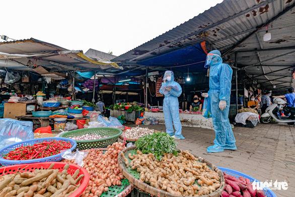 Nhân viên y tế cùng ban quản lý chợ Cầu Mới - Ngã Tư Sở (Hà Nội) đã phát mẫu khai báo dịch tễ đến tận tay người dân và mời xét nghiệm virus corona theo lịch trình giãn cách - Ảnh: NAM TRẦN