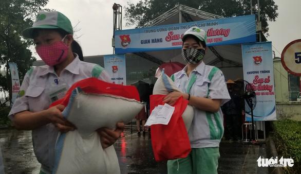 Mưa như trút, công nhân giúp nhau che hạt gạo sẻ chia kẻo ướt - Ảnh 3.