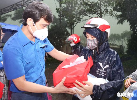 Mưa như trút, công nhân giúp nhau che hạt gạo sẻ chia kẻo ướt - Ảnh 1.